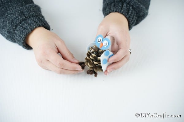 Adding pipe cleaner feet to the pinecone owl craft