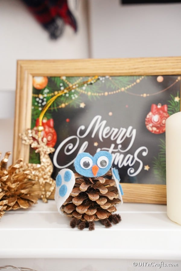 A pinecone owl sitting in front of a Christmas sign