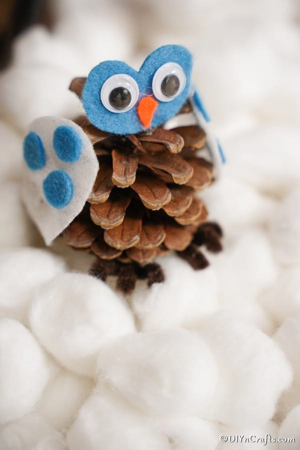 A pinecone owl decoration sitting on a bed of cotton balls
