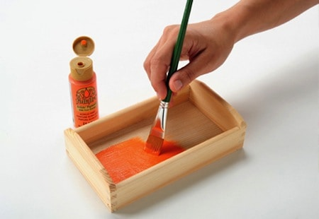Painting a small wooden tray with FolkArt acrylic paint in orange using a paintbrush