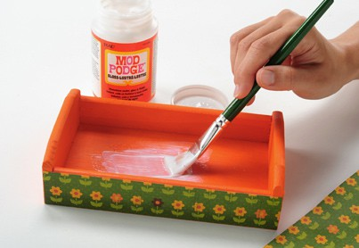 Painting Mod Podge Gloss inside of a painted wood tray with a green handled paint brush