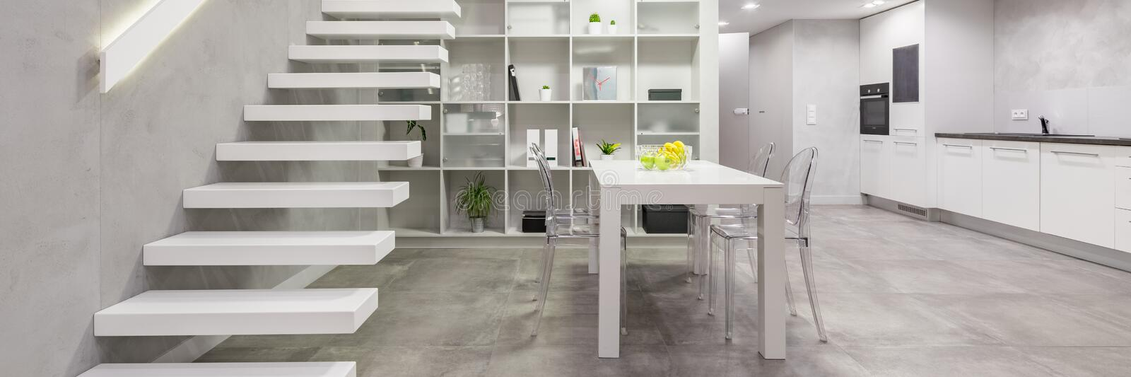 Apartment with modern white staircase. Loft apartment with modern white mezzanine staircase, dining table with chairs and open kitchen stock image