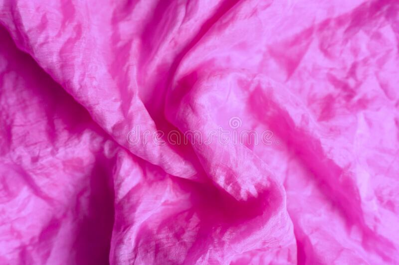 Background of bright pink silk wrinkled fabric cloth. royalty free stock photos
