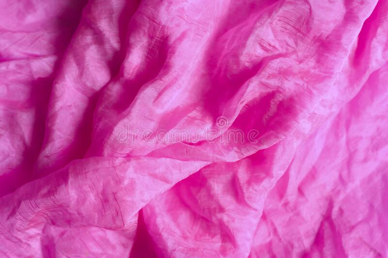 Background of bright pink silk wrinkled fabric cloth. stock photos