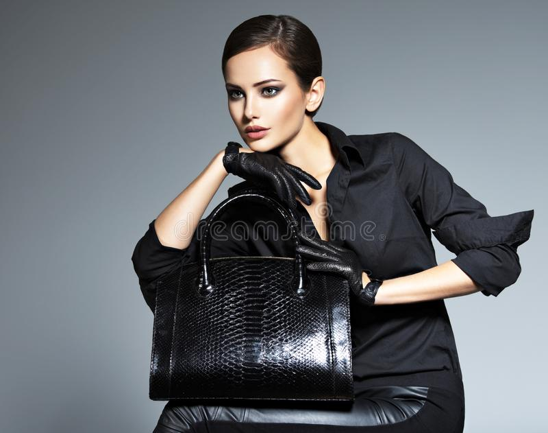 Beautiful woman in black holds fashion handbag. Posing at studio royalty free stock photo