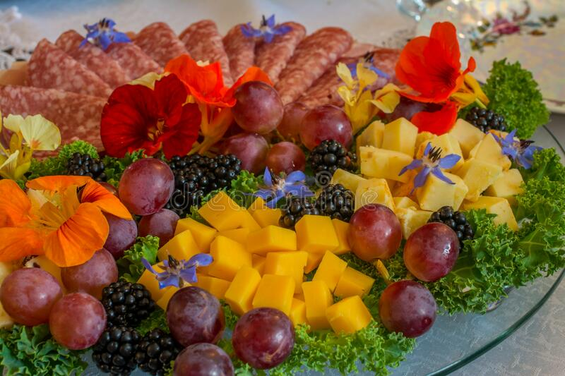 Beautifully decorated home made salads with edible flowers on table with different food snacks party royalty free stock images