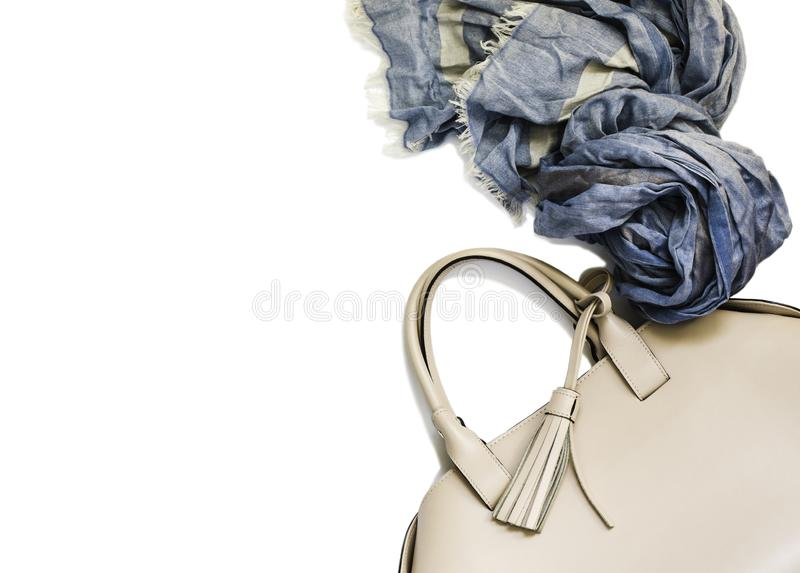 Beige woman`s handbag and blue scarf isolated on white background royalty free stock images
