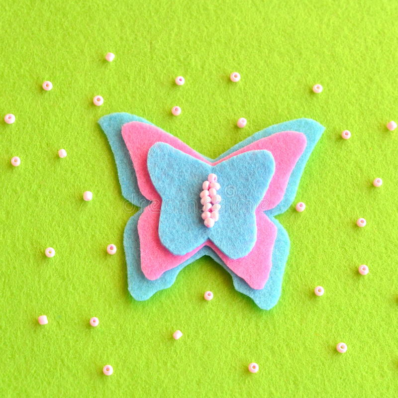 Butterfly decor sewn from pink and blue felt. Spring or summer simple DIY idea for kids stock image