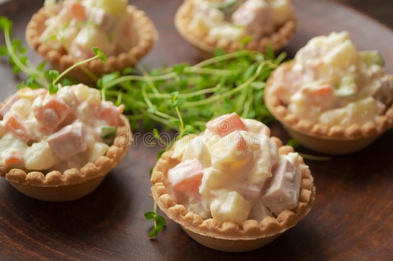 Canapes in tartlets, Russian snack. Wooden background, tartlet with russian salad for catering stock images