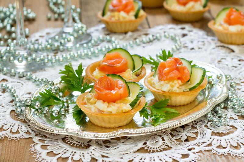 Christmas snack on the festive table. Tartlets with salad, decoration from salmon and cucumber stock photo