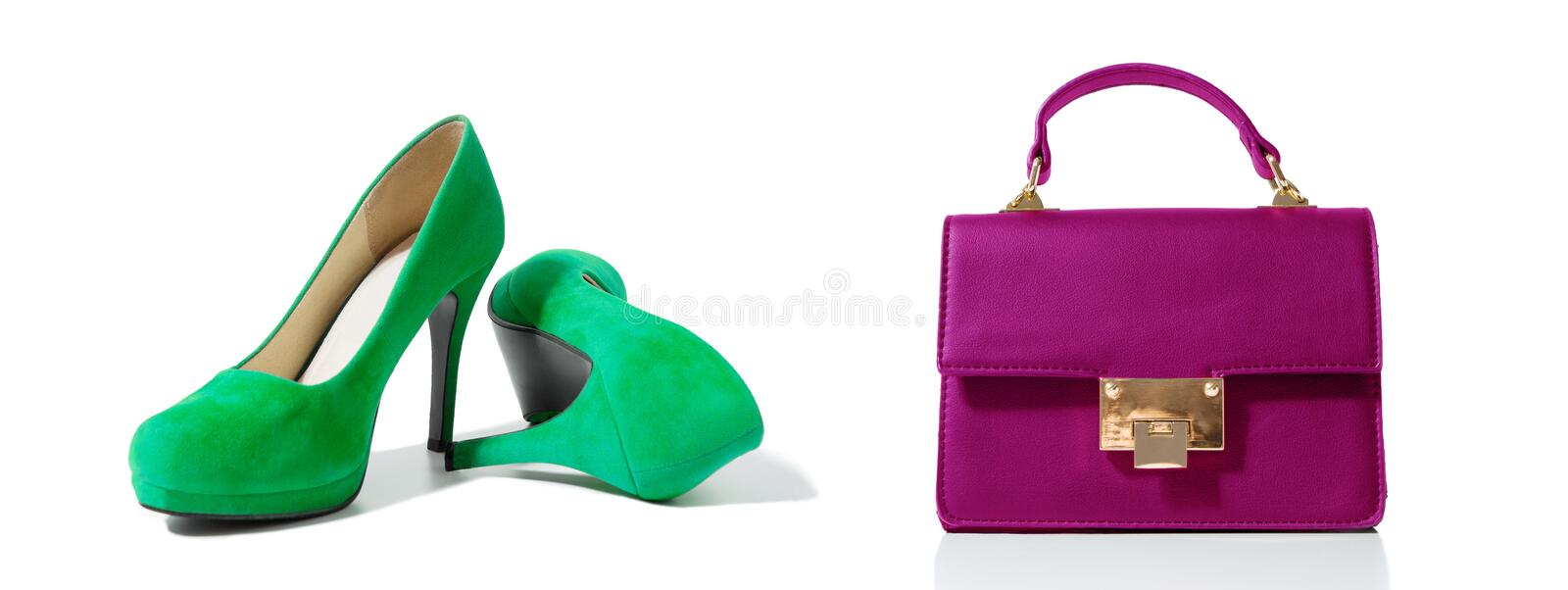 Closeup of fashionable high heels shoes and woman bag isolated on white background. Green color shoe and pink handbag on floor. Shopping and fashion concept royalty free stock photography