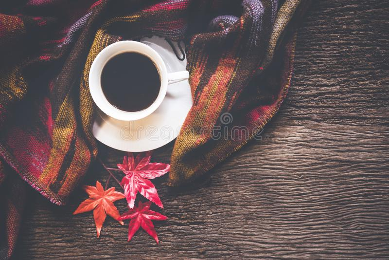 Cozy winter background, cup of hot coffee with marshmallow and leaves maple on season autumn, warm knitted sweater on old wooden b stock photography