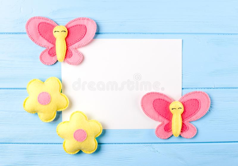 Craft pink and yellow butterfly and flowers with white paper, copyspace on blue wooden background. Hand made felt toys. Abstract s stock photo