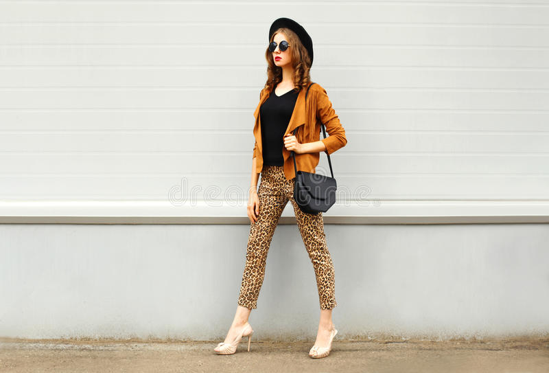 Fashion pretty young woman wearing a retro elegant hat, sunglasses, brown jacket and black handbag walking in city over backg. Fashion pretty young woman wearing royalty free stock photo