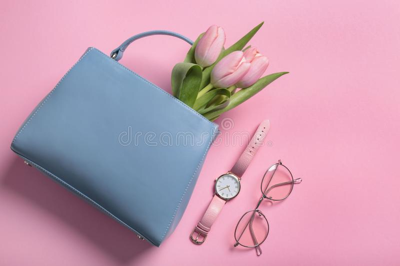 Flat lay composition with stylish woman`s handbag and spring flowers stock photo