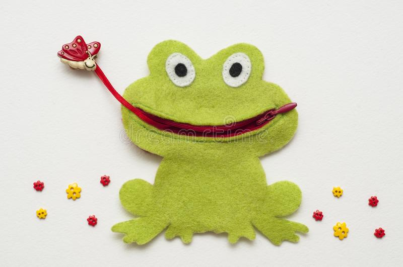Funny felt toy. Green frog caught a butterfly. Handmade toy. stock photo
