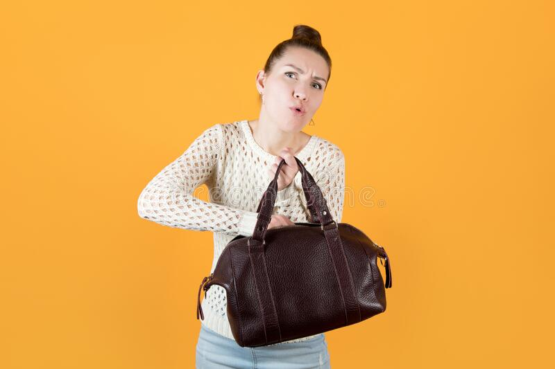 Girl pulls something out of a woman s handbag with effort royalty free stock image