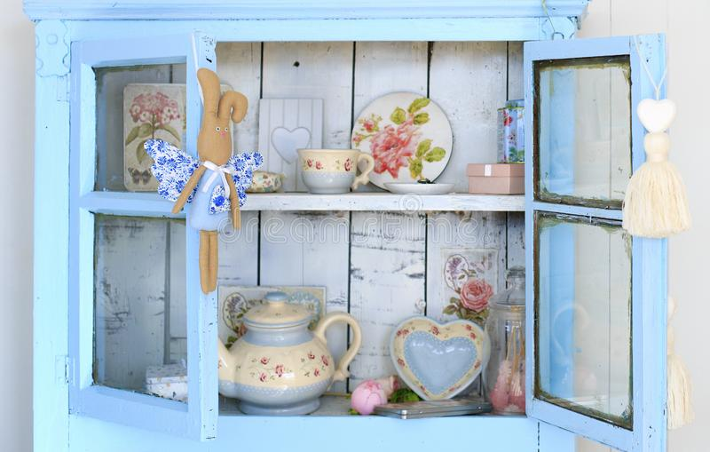 Vintage interior of retro, vintage wooden light blue sideboard and the old beautiful set of dishes stock image