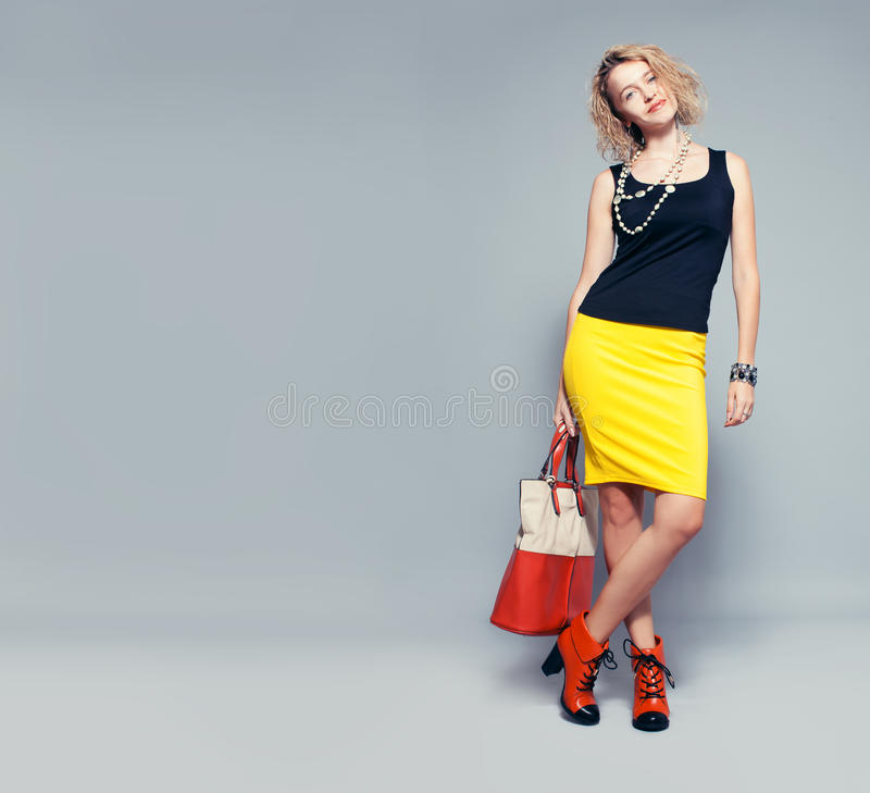 Happy woman with handbag. In studio stock photos