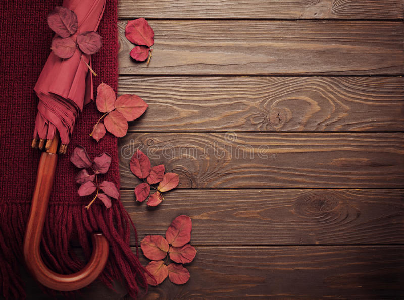Knitted scarf of burgundy color with autumn leaves and an umbrella on a dark wooden background. stock photos