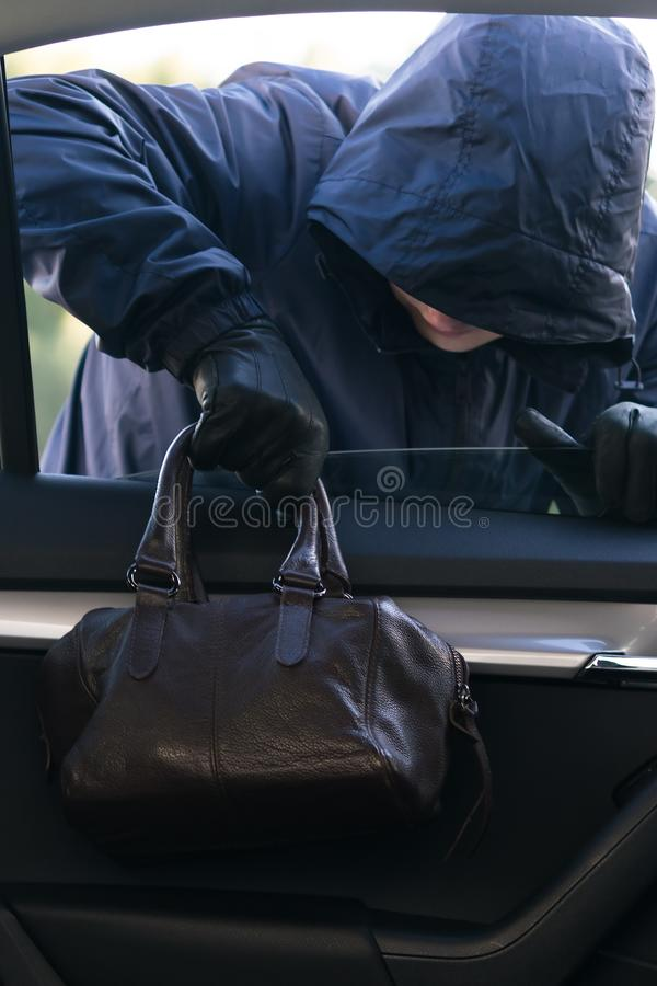 A man in a dark hood is stealing a woman`s handbag through a car window royalty free stock photo