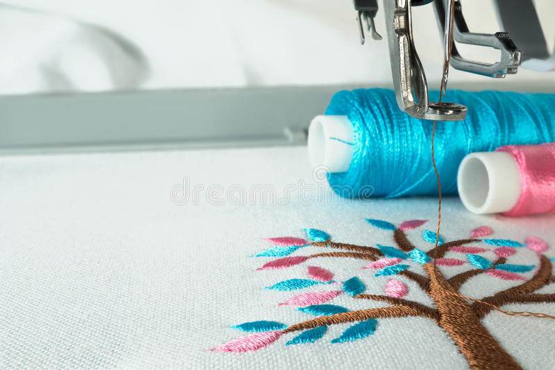 Picture of workspace in the embroidery machine. Close up look under the needle, lovely tree minimal sytle on background have two colorfull thread cyan and pink royalty free stock photo