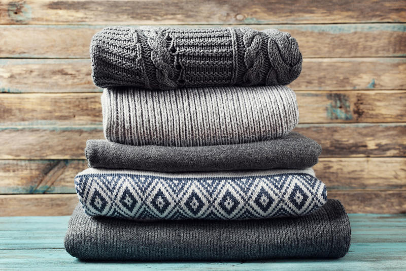 Pile of knitted winter clothes on wooden background, sweaters, knitwear stock photography