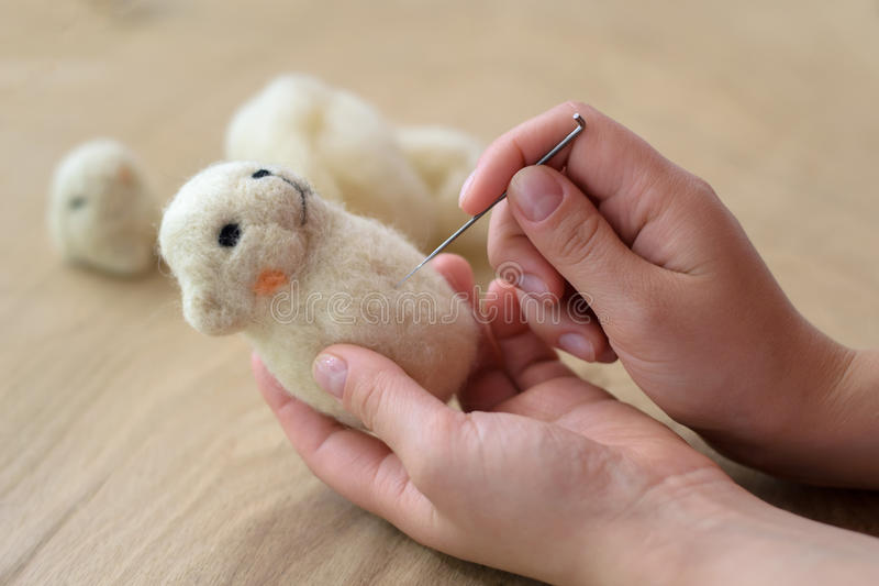 Process of felting a toy from a light wool on a wooden background stock photos