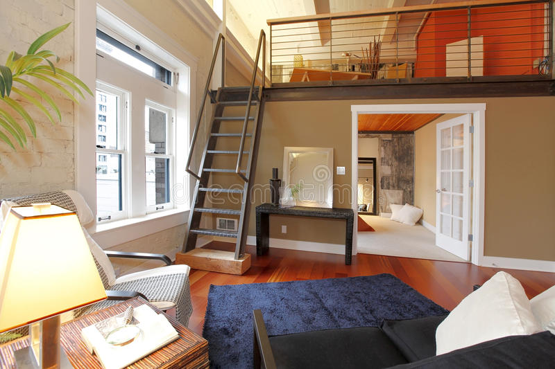 Reconstructed modern living room with mezzanine. View of modern reconstructed living room with mezzanine area above bedroom. View of iron steep stairs stock photography