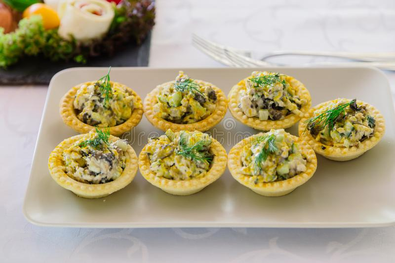 Sandwiches with squid meat salad, cucumber, egg, cheese and mayonnaise. Canapes in tartlets, Russian snack. Delicious royalty free stock image