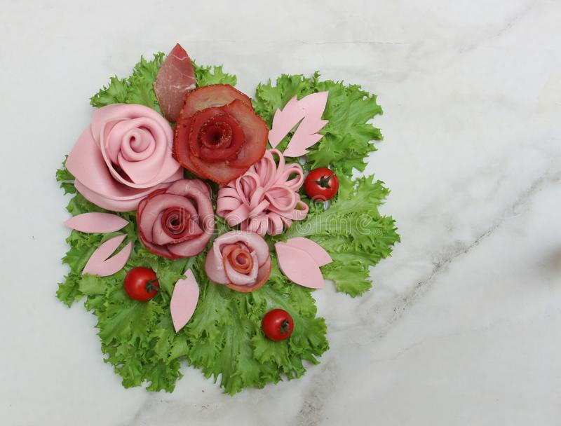 Serving A bouquet of flowers made from meat delicacies, sausages and a fresh leaf of salad royalty free stock images