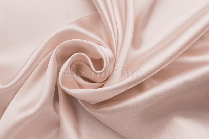 Smooth wrinkled silk bedsheet, fabric background. Abstract crumpled satin texture. Cream color. Folded cloth, wallpaper. Soft wavy stock photography