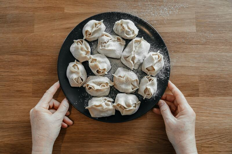 Stuffed homemade dumplings, manti of dough and minced on a dark plate royalty free stock images