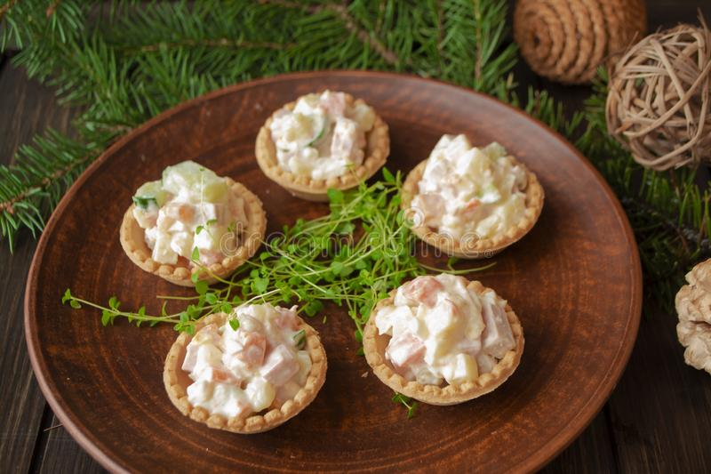 Tartlet with russian salad with potatoes, cucumber, egg, mushrooms and mayonnaise. Christmas table stock image