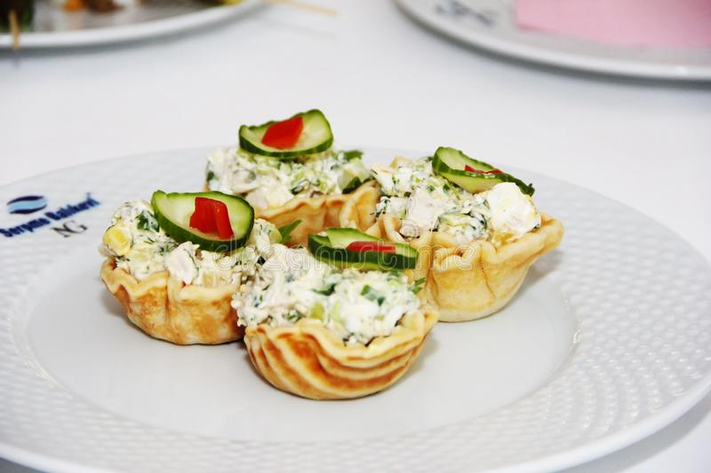 tartlets with salad and green cucumber on white plate stock photo