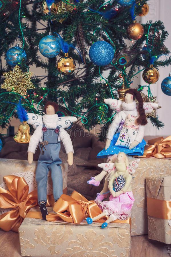 Three funny tilda angels sitting on new year gifts stock photography