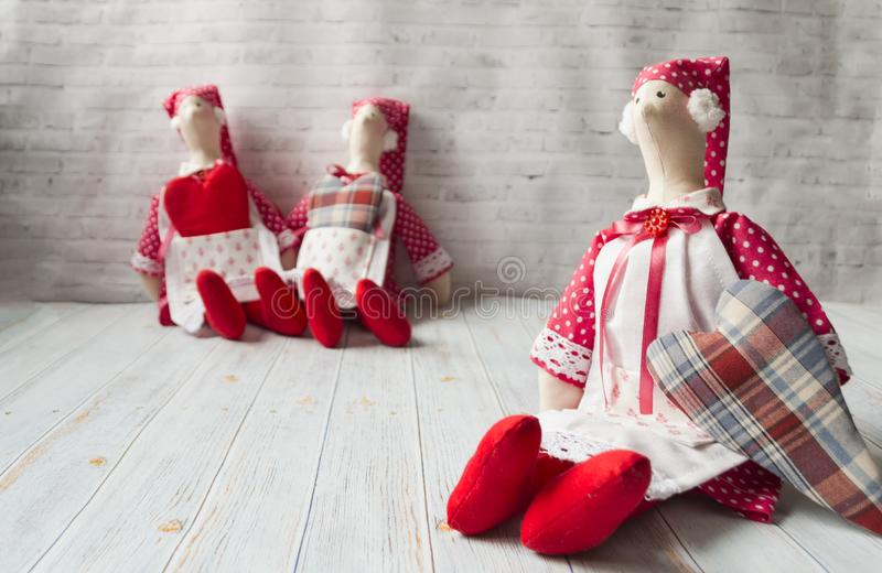 Three tilde dolls in red dresses, and white aprons, and red kalpaks sit on a light background. Interior dolls. There is stock photo