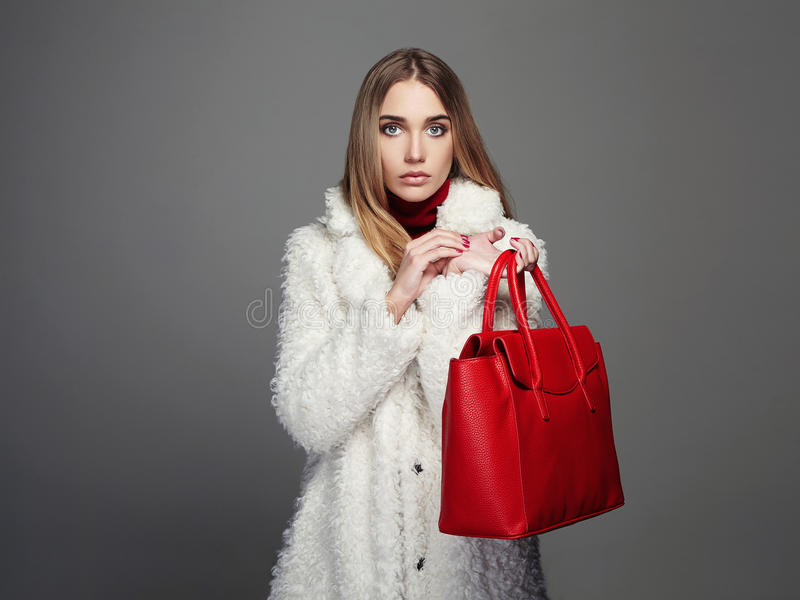 Winter beautiful Woman with red Handbag. Beauty Fashion Model Girl in fur royalty free stock photo
