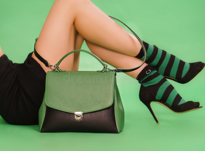 Woman`s handbag and legs in a black nad green colors stock photography