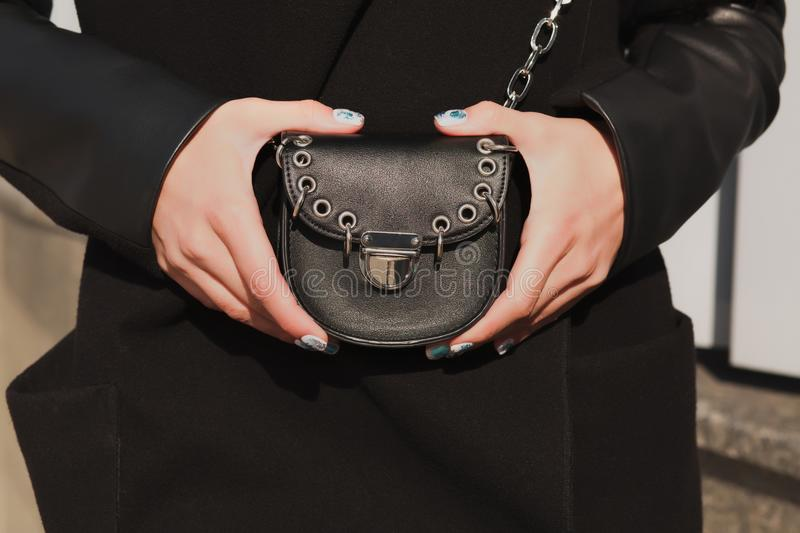 Woman`s hands holding small fashionable handbag at the backgroun stock images