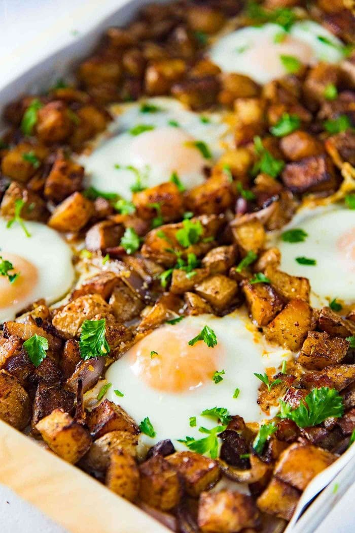 Sheet pan Breakfast Potatoes with Bacon and Eggs - This oven roasted breakfast potatoes and eggs with crispy bacon bits, is all cooked in the same sheet pan so you can enjoy your weekend mornings without standing over the stove.